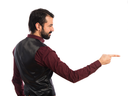 lateral: Man wearing waistcoat pointing to the lateral