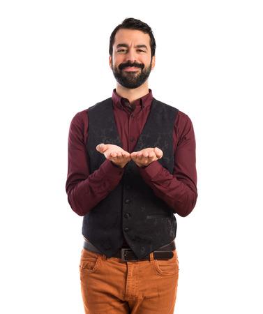 Man wearing waistcoat holding something photo
