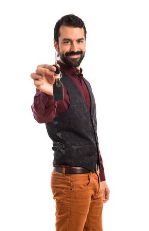 Man wearing waistcoat holding car key photo