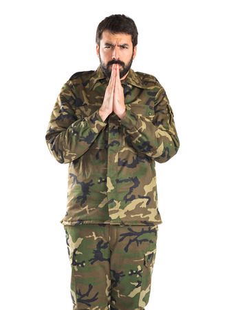 pleading: Soldier pleading over white background Stock Photo