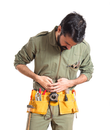 stomachache: Mechanic with stomachache over white background