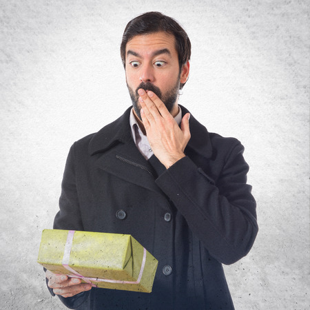 surprised man: Surprised man holding a gift