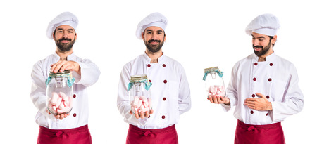Angry chef holding jar glass with sweetmeats inside photo