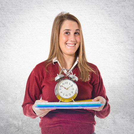 Student holding a clock over white background photo