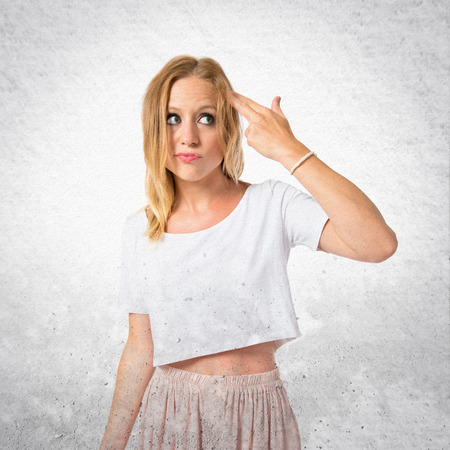 Girl making suicide gesture over white background photo