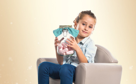Blonde girl holding jar glass with sweetmeats inside photo