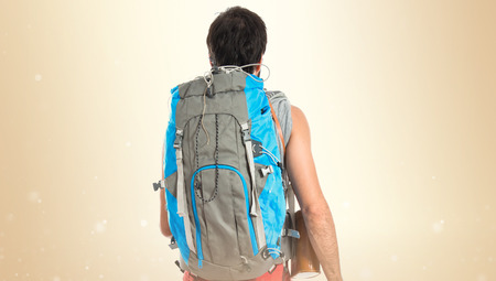 Young backpacker walking over white background photo