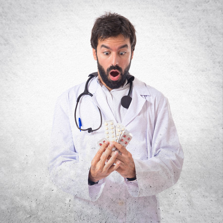 doctor holding pills: Surprised doctor holding pills over white background Stock Photo