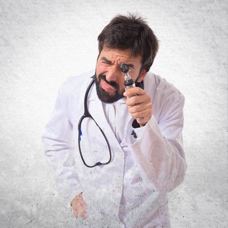 dolor de oido: Otorrinolaring�logo con su otoscopio sobre fondo blanco Foto de archivo