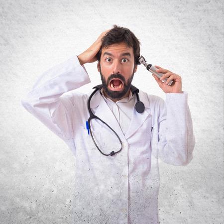 dolor de oido: Otorrinolaringólogo loco con su otoscopio sobre fondo blanco