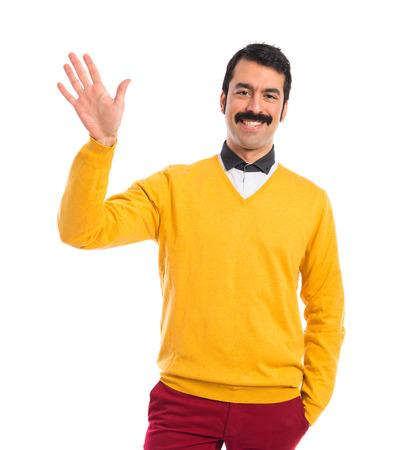 personas saludando: Hombre con bigote saludando sobre fondo blanco Foto de archivo