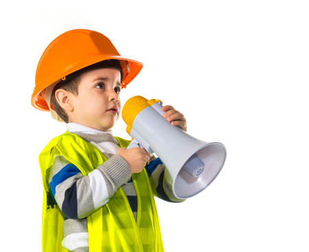 Kid dressed like workman shouting by megaphone Stock Photo