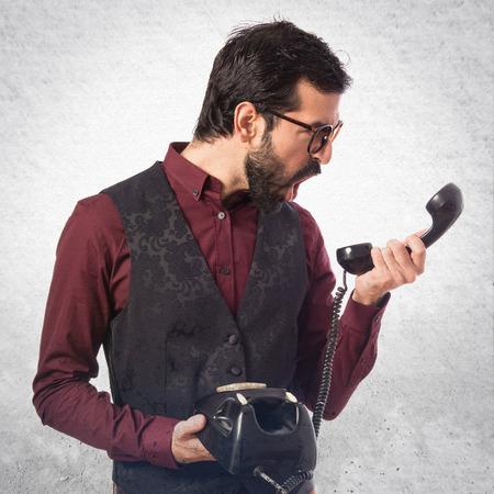 waistcoat: Man wearing waistcoat talking to vintage phone