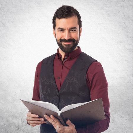 waistcoat: Man wearing waistcoat reading book Stock Photo