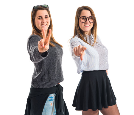 Twin sisters pointing to the front and doing victory gesture photo