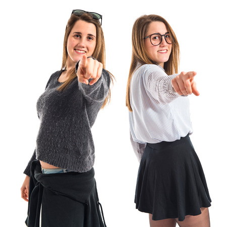 preppy: Twin sisters pointing to the front Stock Photo