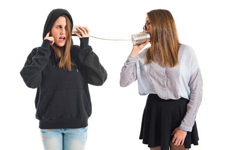 Twin sisters talking through tin phone photo