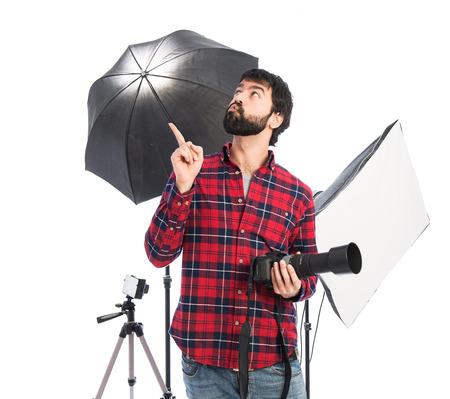 Photographer thinking over white background photo