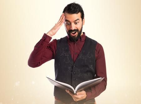 waistcoat: surprise man wearing waistcoat reading book Stock Photo