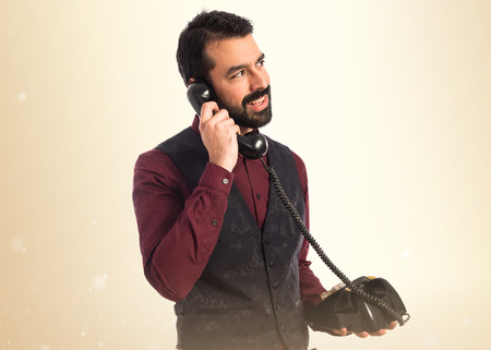 old cell phone: Man wearing waistcoat talking to vintage phone