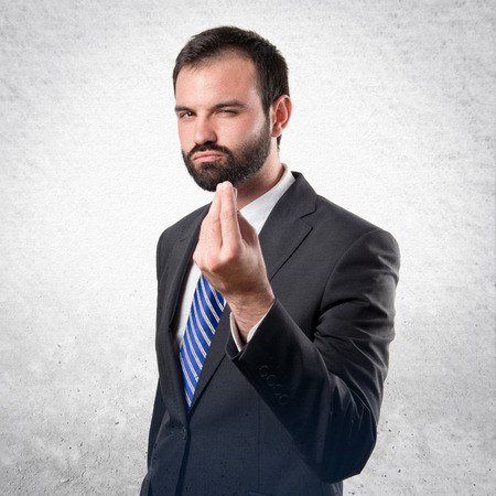 Young businessman doing a money gesture over white background photo