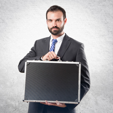 Young businessman with his briefcase over white background photo