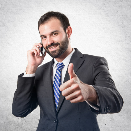 Young businessmen talking to mobile over isolated background. photo