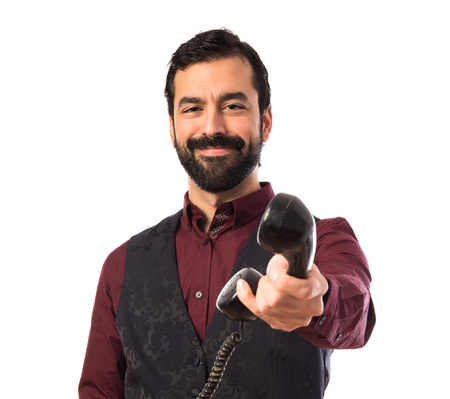 important phone call: Man wearing waistcoat talking to vintage phone