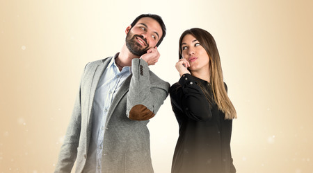 couple talking: Couple talking to mobile over isolated background. Stock Photo