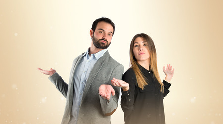 unimportant: Couple making unimportant gesture over  white background
