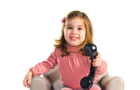old phone: Kid sitting on armchair talking with vintage phone