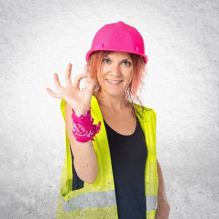mujer trabajadora: Mujer del trabajador que hace la muestra Ok sobre fondo blanco
