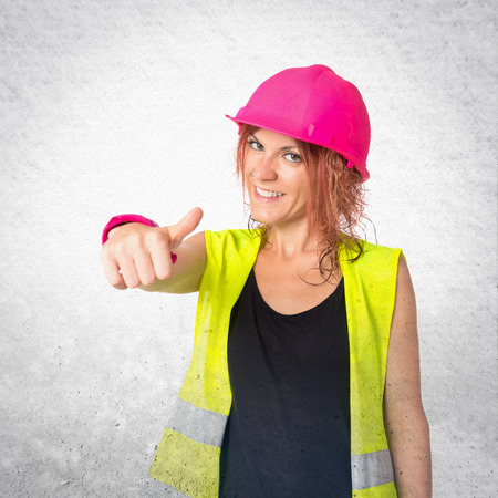 Worker woman making Ok sign over white background photo