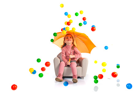 Kid with umbrella sitting on armchair photo