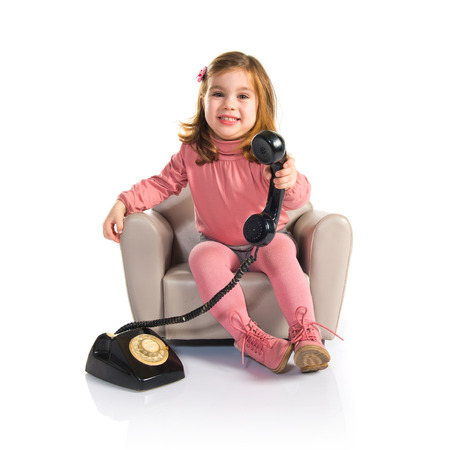 Kid sitting on armchair talking with vintage phone photo