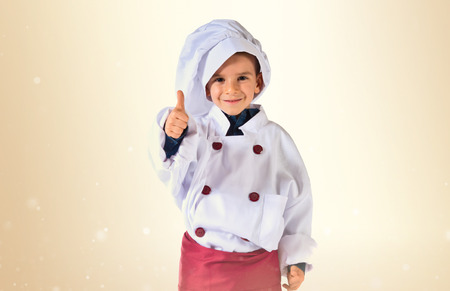 as: child dressed as a chef with thumb up