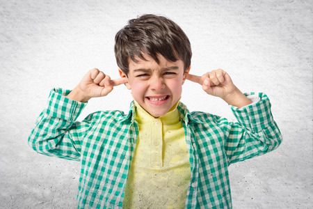 by ear: Boy covering his ears over white background. Stock Photo