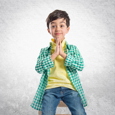 supplication: Blonde boy pleading over isolated white background