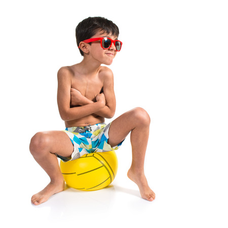 Child sitting on soccer ball photo