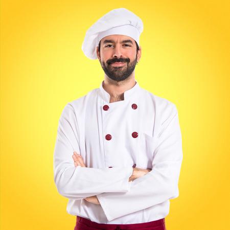 Cocinero con los brazos cruzados sobre el fondo blanco