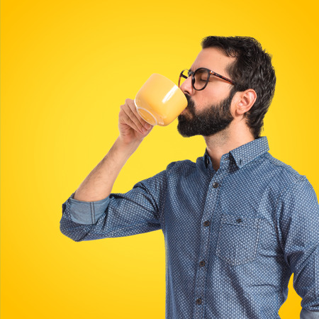 drinking coffee: Young hipster man drinking coffee over white background