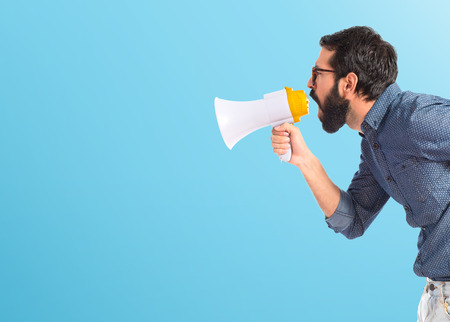 speaking: Young hipster man shouting by megaphone Stock Photo