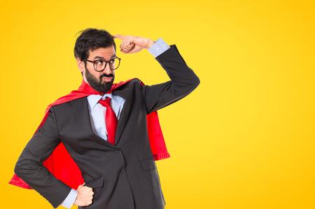 gente loca: El hombre de negocios vestido como superhéroe que piensa sobre blanco
