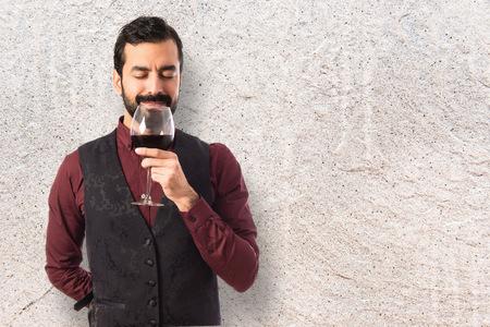 waistcoat: Man wearing waistcoat holding a wine glass Stock Photo