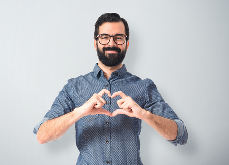 young people: Young hipster man making heart sign Stock Photo