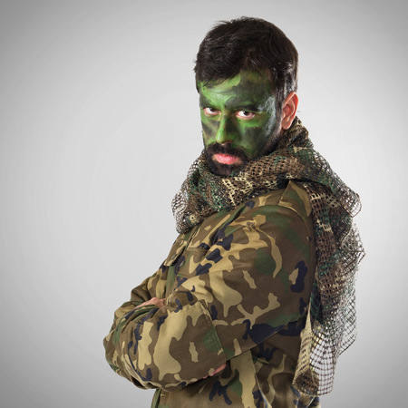 cross armed: soldier with his face painted Stock Photo