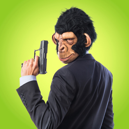 holding gun to head: Monkey man with a gun