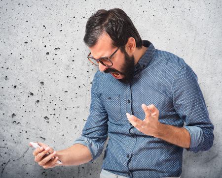 Furious hipster man talking to mobile photo