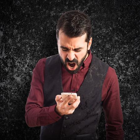 waistcoat: Man wearing waistcoat shouting by mobile