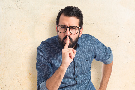 secret: Young hipster man making silence gesture Stock Photo